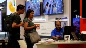 Shoppare som ser ny TV för att köpa och frågar arbetare stock video