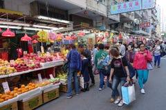 Shoppareköpet bär frukt på den Kowloon stadsmarknaden i Hong Kong arkivbild