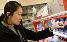 Shopparen bläddrar en hylla i ett skönhetsmedellager royaltyfri bild