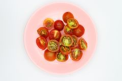 Shopped tomatoes in pink dish on white background royalty free stock images