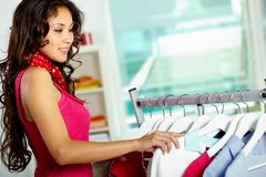 Shopper. Portrait of happy woman looking through new collection in clothing departmant Royalty Free Stock Images