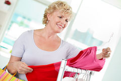 Shopper. Portrait of middle aged woman choosing new tanktop in clothing departmant Stock Photo
