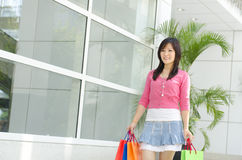 Shopper. Asian young shopper walking out from shopping mall stock images