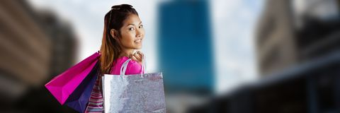 Shopper with bags looking over shoulder against blurry city Royalty Free Stock Photography