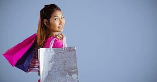 Shopper with bags looking over shoulder against purple background Stock Images