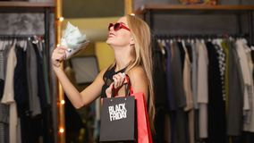 Shopper with Bags and Money. Joyful female shopper holding lots of money and bags on black friday as buying clothes in expensive designer shop stock video