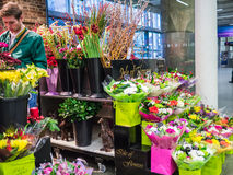 Shopper and bouquets at Isle of Flowers, St Pancras Station, London, UK. Royalty Free Stock Photography