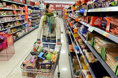 Shopper Browses Supermarket Aisle Royalty Free Stock Photos
