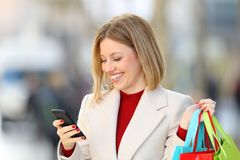 Shopper buying on line holding shopping bags Stock Photography