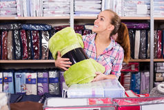 Shopper buying new blanket and coverlet in textile store. Young woman shopper buying new blanket and coverlet in textile store stock images