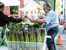 Shopper buys asparagus bundle at Farmers Market, Corvallis, Oreg Royalty Free Stock Images