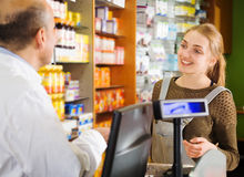 Shopper buys medicine. Positive shopper buys medicine in a pharmacy stock images