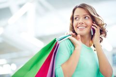 Shopper calling. Pretty shopper with paperbags speaking on the phone royalty free stock photos