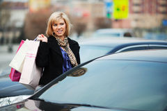 Fashion woman with shopping bags on car parking Royalty Free Stock Images