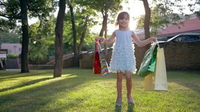 Shopper child into high-heeled shoes take pleasure new purchases after visiting expensive boutiques and carries lot. Paper bags into hands outdoors in backlight stock video footage
