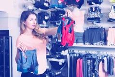 Shopper is choosing sports underwear. In lingerie shop Royalty Free Stock Image