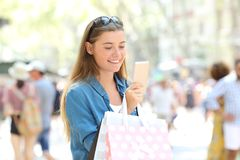 Shopper consulting online offers in a phone. Shopper holding shopping bags consulting online offers in a smart phone in the street Royalty Free Stock Images