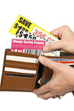 Shopper With Coupons. A female shopper pulls coupons from her wallet in order to save some money Royalty Free Stock Photography