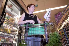 Shopper with Coupons. Woman shopping in grocery store aisle holding shopping list and coupons Royalty Free Stock Photography
