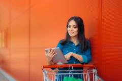 Shopping Woman with PC Tablet and Pushcart Near Store. Shopper girl online shopping and paying Royalty Free Stock Image