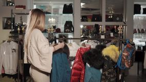 Young woman is trying on a warm winter jacket in a clothes store. Shopper girl is throwing on her shoulders denim jacket in a shop hall. She is stroking fur and stock video