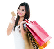 Shopper Holding Credit Card And Shopping Bags. Portrait of a cute young woman holding credit card and shopping bags against white background Royalty Free Stock Photos