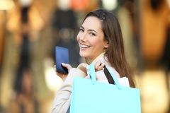 Shopper holding phone and shopping bags looking at you Stock Photography