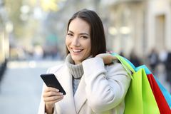 Shopper holding a phone and shopping bags in winter. Happy shopper holding a smart phone and colorful shopping bags in winter in the street stock images