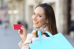 Shopper holding shopping bags and credit card. Portrait of a happy shopper holding shopping bags and credit card on the street Stock Photo