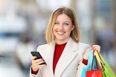 Shopper holding shopping bags and phone looking at camera Stock Photo