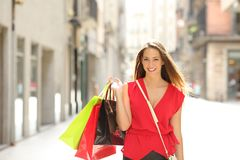 Shopper holding shopping bags walking towards camera. Front view portrait of a happy shopper walking towards camera holding shopping bags looking at you stock images