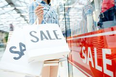 Sale in the mall. Shopper holds paperbags with sale announcement while standing by window display in modern mall Royalty Free Stock Image