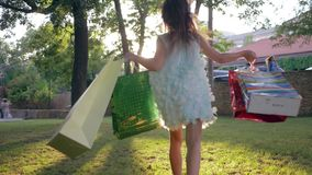 Shopper kid rejoices new buys after visiting expensive store and with many packages into hands runs through park. In backlight stock footage