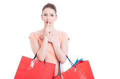 Shopper lady with finger on lips gesture like being quiet Stock Images