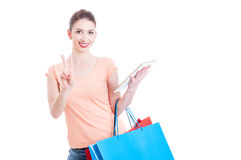 Shopper lady smiling and showing peace sign holding a tablet Royalty Free Stock Images