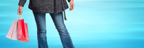 Shopper lower body with bags against blurry blue background Royalty Free Stock Images