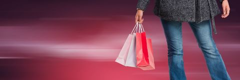Shopper lower body with bags against blurry dark red background. Digital composite of Shopper lower body with bags against blurry dark red background Stock Image