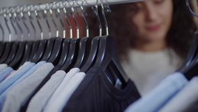 Shopper is moving hangers with tee shirts in sportive clothing store, close-up