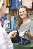 Shopper Paying For Goods Using Credit Card Machine Royalty Free Stock Image