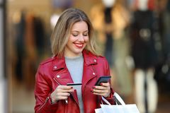Shopper paying on line with a card in a mall. Happy fashion blonde shopper wearing a red jacket paying on line with a credit card and a smart phone in a mall Stock Images