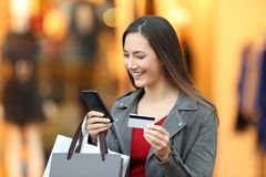 Shopper paying on line with credit card in a mall. Portrait of a happy shopper paying on line with credit card in a mall Royalty Free Stock Images
