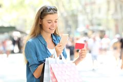 Shopper paying online with credit card in the street. Happy whopper paying online with credit card and a smart phone in the street Stock Images
