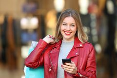 Shopper posing holding a phone and shopping bags. Happy shopper posing holding a smart phone and shopping bags in the street with a storefront in the background Stock Photography