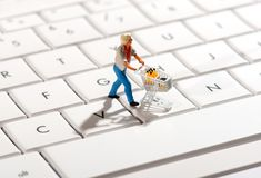 Shopper pushing a trolley over a computer keyboard Royalty Free Stock Image