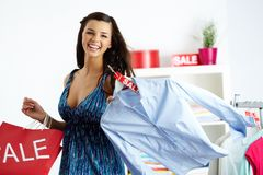 Shopper with shirt. Portrait of happy shopper with bags and shirt in clothing department stock images