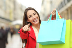 Shopper with shopping bags pointing you royalty free stock photography