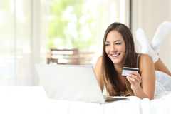 Shopper shopping online with credit card and laptop. On the bed at home Stock Photography