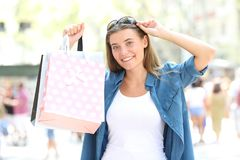 Shopper showing blank shopping bags in the street. Front view portrait of a happy shopper showing blank shopping bags in the street Royalty Free Stock Image