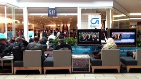 Shopper sitting rest area and watching TV stock footage