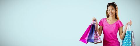Shopper smiling with bags against light blue background Stock Image